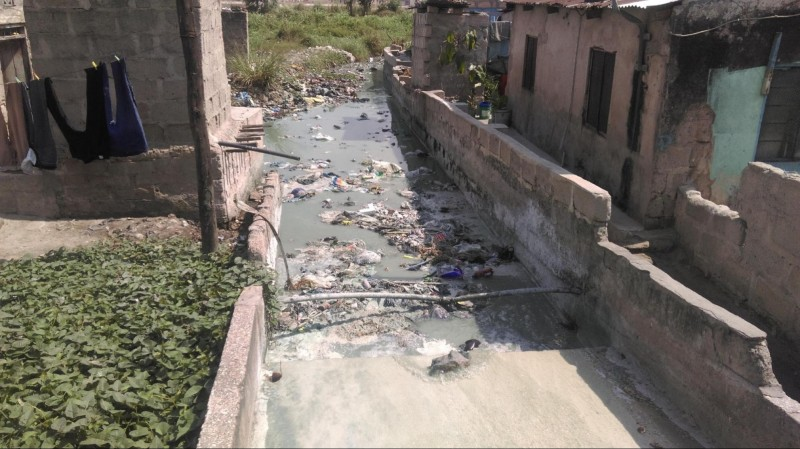 wastewater pouring down and collecting into a pool next in between people's homes